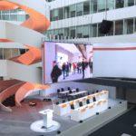 Hauptversammlung - Weitwinkel-Aufnahme gesamte Veranstaltungsfläche mit Leinwand und Rednertischen