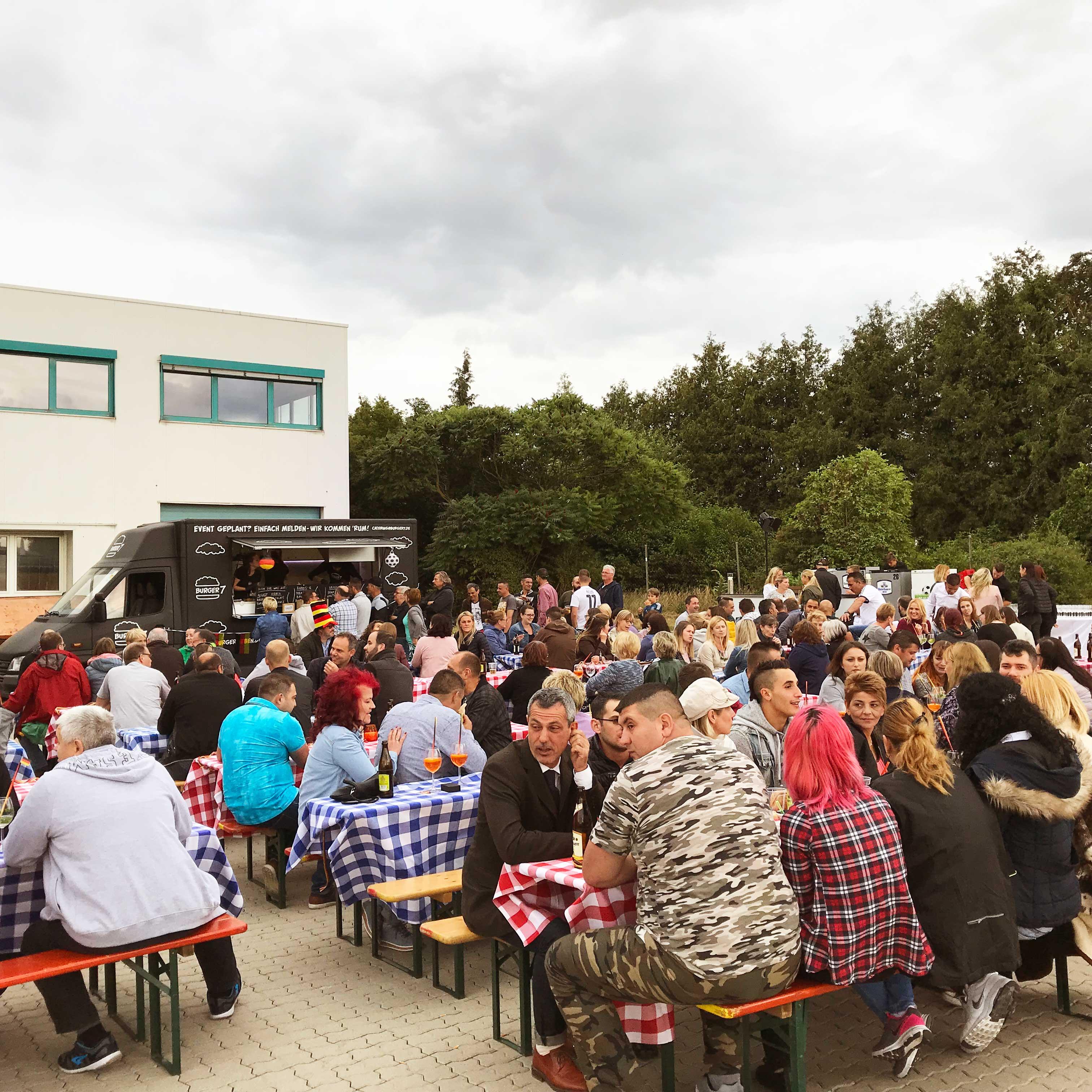 Eventorganisation: Außenansicht Eventlocation mit Gästen und Foodtrucks